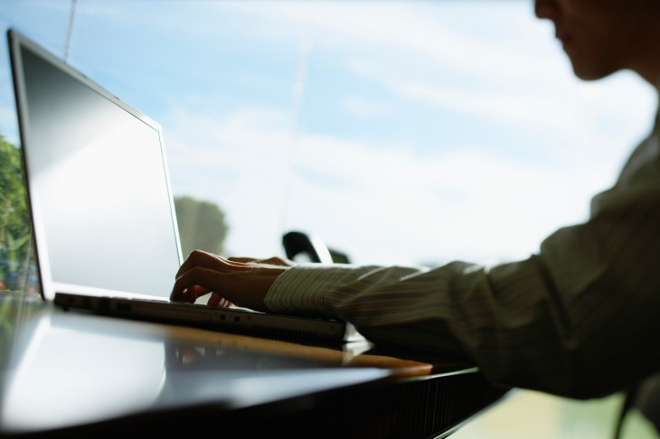 Businessman Using Laptop --- Image by © Simon Jarratt/Corbis